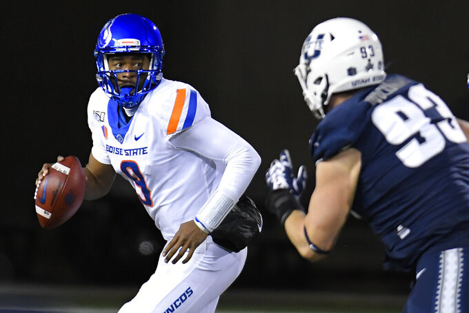 Boise State quarterback Jaylon Henderson (9) looks for a receiver as Utah State defensive end Jacoby Wildman (93) pursues during the first half of an NCAA college football game Saturday, Nov. 23, 2019, in Logan, Utah. (AP Photo/Eli Lucero)