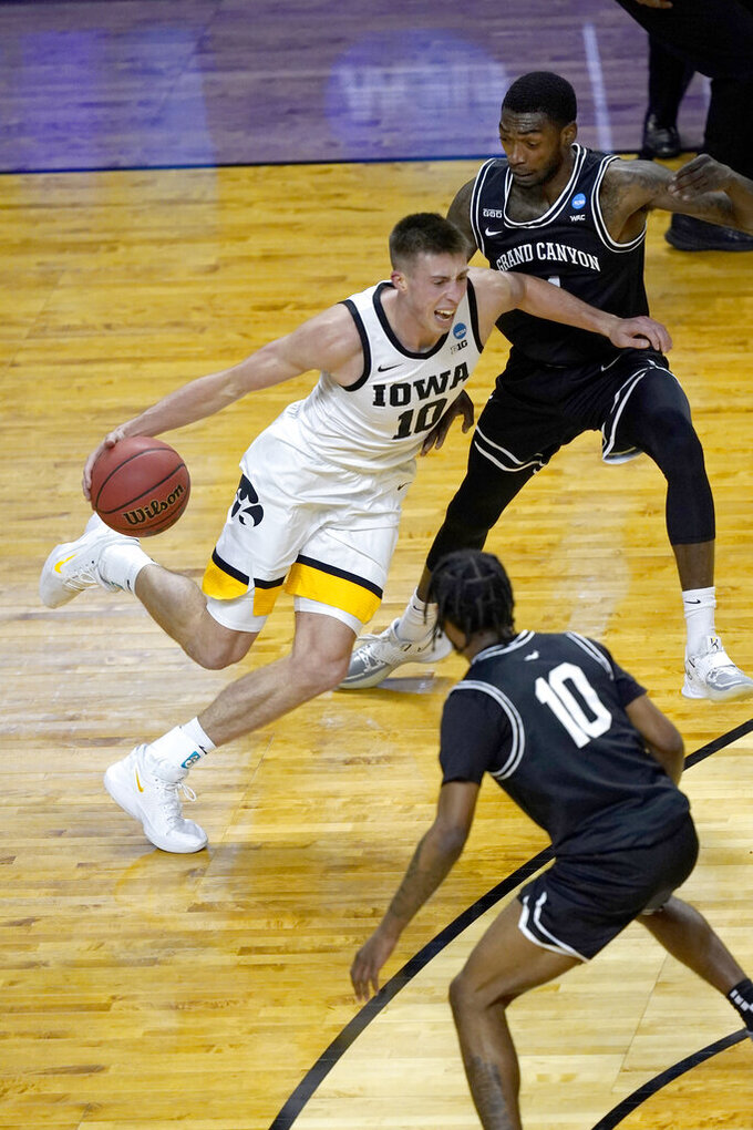 Iowa's Joe Wieskamp (10) drives to the basket between Grand Canyon's Jovan Blacksher Jr. (10) and Oscar Frayer during the first half of a first round NCAA college basketball tournament game Saturday, March 20, 2021, at the Indiana Farmers Coliseum in Indianapolis. (AP Photo/Charles Rex Arbogast)