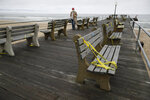 Caution tape is wrapped around benches to discourage sitting at a nearly empty beach Saturday, May 23, 2020, in Ocean Grove, N.J., during the coronavirus pandemic. (AP Photo/John Minchillo)