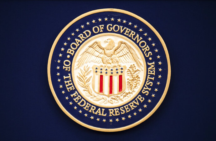FILE - This July 31, 2019, file photo, shows the Federal Reserve logo ahead of the start of a scheduled news conference by Chairman Jerome Powell in Washington. The Federal Reserve says it purchased $1.3 billion in corporate bonds in late June 2020 as part of its effort to keep U.S. interest rates low and ensure large companies can borrow by selling bonds. (AP Photo/Manuel Balce Ceneta, File)