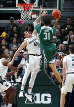 Eastern Michigan's Ty Groce (31) goes up against the defense of Michigan State's Conner George (41) during the second half of an NCAA college basketball game, Saturday, Dec. 21, 2019, in East Lansing, Mich. (AP Photo/Al Goldis)