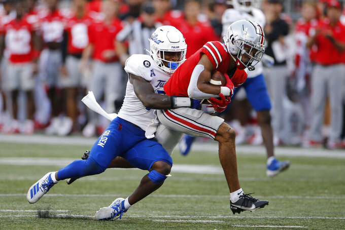 Tulsa defensive back TieNeal Martin, left, tackles Ohio State receiver Chris Olave during the second half of an NCAA college football game Saturday, Sept. 18, 2021, in Columbus, Ohio. (AP Photo/Jay LaPrete)