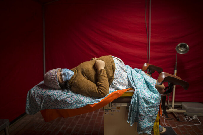 Olinda Tafur, 20, lies on an examination table as she waits to be seen by obstetrician Dr. Osvaldo Sierra inside a tent set up in the emergency area of the National Perinatal and Maternal Institute to receive women in labor who are infected with COVID-19 in Lima, Peru, Wednesday, July 29, 2020. Just before giving birth to her first child, Tafur learned that she had tested positive for the new coronavirus upon arriving with labor pains to the emergency area. (AP Photo/Rodrigo Abd)
