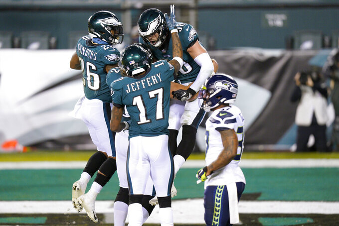 Philadelphia Eagles' Dallas Goedert (88) celebrates with Alshon Jeffery (17) and Miles Sanders (26) after scoring a touchdown during the first half of an NFL football game against the Seattle Seahawks, Monday, Nov. 30, 2020, in Philadelphia. (AP Photo/Chris Szagola)