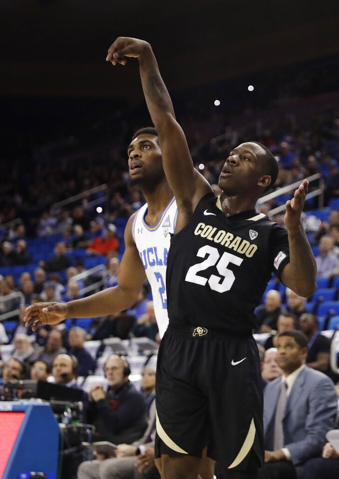 Colorado 's McKinley Wright IV (25) follows through as he makes a 3-point basket over UCLA forward Cody Riley, left, during the first half of an NCAA college basketball game Wednesday, Feb. 6, 2019, in Los Angeles. (AP Photo/Marcio Jose Sanchez)