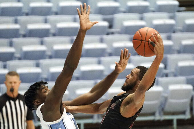 North Carolina forward Day'Ron Sharpe guards North Carolina Central guard Nicolas Fennell, right, during the second half of an NCAA college basketball game in Chapel Hill, N.C., Saturday, Dec. 12, 2020. (AP Photo/Gerry Broome)