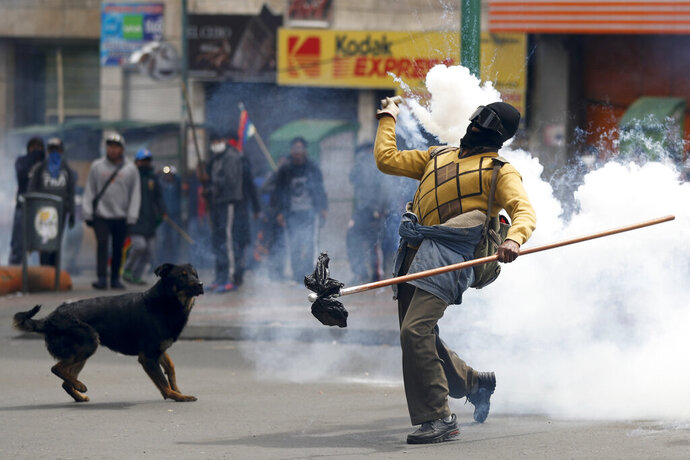 A backer of former President Evo Morales returns a tear gas canister to police during clashes in La Paz, Bolivia, Wednesday, Nov. 13, 2019. Bolivia's new interim president Jeanine Anez faces the challenge of stabilizing the nation and organizing national elections within three months at a time of political disputes that pushed Morales to fly off to self-exile in Mexico after 14 years in power. (AP Photo/Natacha Pisarenko)