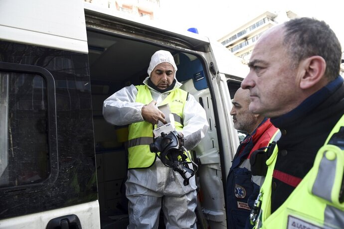 Paramedics prepare to enter a college after employees received a suspicious envelope,  in the northern port city of Thessaloniki, Greece, Friday, Jan. 11, 2019. At least nine people have received medical attention after about a dozen letters containing a white powder described as consisting of