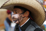 A man wearing a protective face mask walks amidst outdoor stalls at the Mercado Sonora, which reopened ten days ago with measures to reduce congestion and limit the spread of the new coronavirus, in Mexico City, Thursday, June 25, 2020.  With Latin America now the epicenter of the pandemic, but with hundreds of millions relying on these markets for food and livelihoods, the debate now centers on whether and how they can ever operate safely. (AP Photo/Rebecca Blackwell)