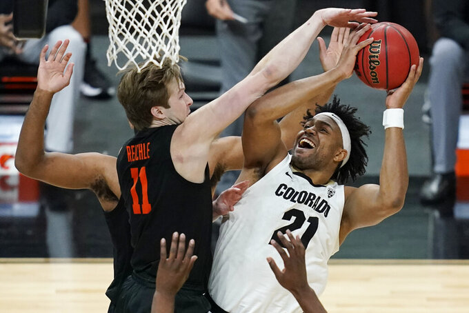 Colorado's Evan Battey (21) shoots around Oregon State's Zach Reichle (11) during the first half of an NCAA college basketball game in the championship of the Pac-12 men's tournament Saturday, March 13, 2021, in Las Vegas. (AP Photo/John Locher)