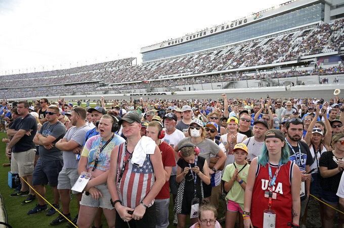 Fans wait for driver introductions before a NASCAR Cup Series auto race at Daytona International Speedway, Saturday, Aug. 28, 2021, in Daytona Beach, Fla. (AP Photo/Phelan M. Ebenhack)
