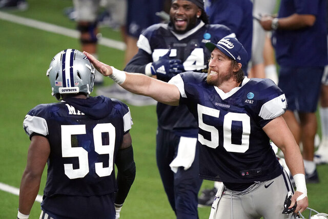 Dallas Cowboys line back Sean Lee (50) pats the helmet of fellow line backer Justin March (59) after March delivered a defensive stop against the offense during an NFL training camp practice in Frisco, Texas, Thursday, Aug. 27, 2020. (AP Photo/LM Otero)