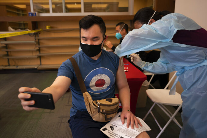 FILE - In this April 12, 2021, file photo, Freeson Wong, 31, takes a selfie as he receives a dose of the Moderna vaccine at a vaccination center in the Chinatown neighborhood of Los Angeles. The global death toll from the coronavirus topped a staggering 3 million people Saturday, April 17, 2021, amid repeated setbacks in the worldwide vaccination campaign and a deepening crisis in places such as Brazil, India and France. (AP Photo/Jae C. Hong, File)