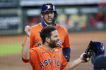 Houston Astros' Jose Altuve, bottom, and Carlos Correa, top, celebrate after scoring on the throwing error by Los Angeles Angels starting pitcher Jose Suarez during the first inning of the first game of a doubleheader baseball game Tuesday, Aug. 25, 2020, in Houston. (AP Photo/Michael Wyke)