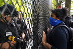 A demonstrator watches as a U.S. Secret Service police office works on a fence blocking Lafayette Park as protests in the death of George Floyd continue, Tuesday, June 2, 2020, near the White House in Washington. Floyd died after being restrained by Minneapolis police officers. (AP Photo/Evan Vucci)