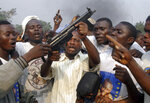 FILE - In this July 27, 2006 file photo shot by AP contributing photographer John Bompengo, looters hold up a gun that was taken from a nearby Church before it was set on fire by supporters of presidential candidate Jean-Pierre Bemba during a rally in Kinshasa, Democratic Republic of Congo. Relatives say longtime Associated Press contributor John Bompengo has died of COVID-19 in Congo's capital. Bompengo, who had covered his country's political turmoil over the course of 16 years, died Saturday, June 20, 2020 at a Kinshasa hospital. (AP Photo/John Bompengo, file)