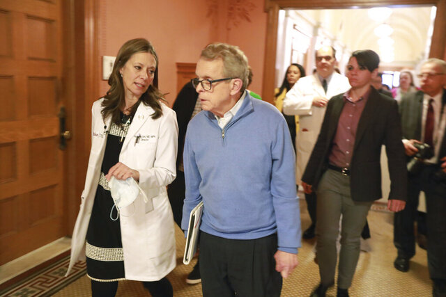 Ohio Department of Health director Amy Acton, left, and Ohio Governor Mike DeWine talk before stepping into a coronavirus news conference Saturday, March 14, 2020 at the Ohio Statehouse in Columbus. (Doral Chenoweth/The Columbus Dispatch via AP)