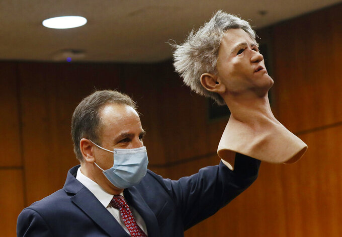 Deputy District Attorney Habib A. Balian holds a rubber latex mask, worn by Robert Durst when police arrested him, Wednesday, Sept. 8, 2021 in Inglewood, Calif. Robert Durst is a champion at running from responsibility, covering his tracks with lies so numerous he couldn't keep them all straight, a prosecutor said Wednesday during closing arguments in the New York real estate heir's murder trial. (Al Seib/Los Angeles Times via AP, Pool)