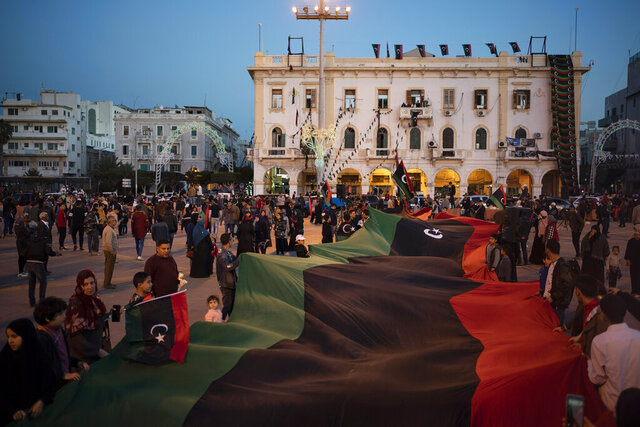 People carry a giant Libyan flag at the Martyr square during a march commemorating the anniversary of anti-Gadhafi protests in Tripoli, Libya, Tuesday, Feb. 25, 2020. (AP Photo/Felipe Dana)