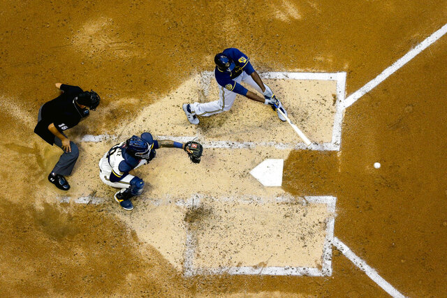 FILE - In this July 14, 2020, file photo, Milwaukee Brewers' Lorenzo Cain, right, hits a single during an intrasquad game at Miller Park in Milwaukee. As baseball attempts to play a shortened 60-game regular season amid a coronavirus pandemic, there is some concern that home plate could become a hot spot for transmission. (AP Photo/Morry Gash, File)