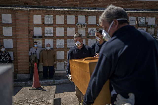 The daughter and husband, center left, no names available, of an elderly victim of the COVID-19 stand as undertakers place the coffin in the grave at the Almudena cemetery in Madrid, Spain, Saturday March 28, 2020. In Spain, where stay-at-home restrictions have been in place for nearly two weeks, the official number of deaths is increasing daily. The new coronavirus causes mild or moderate symptoms for most people, but for some, especially older adults and people with existing health problems, it can cause more severe illness or death. (AP Photo/Olmo Calvo)