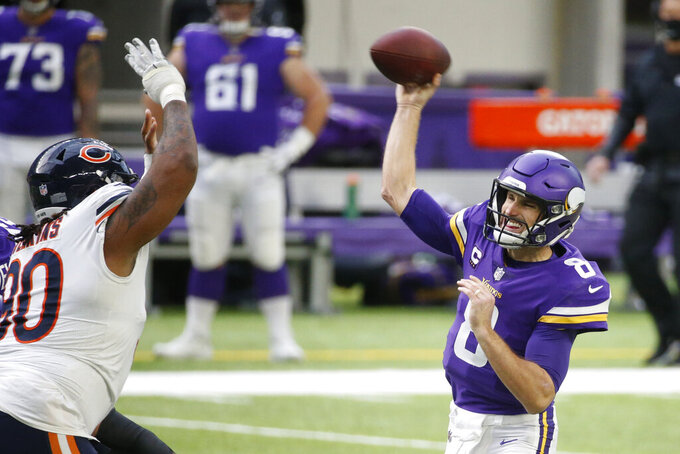 Minnesota Vikings quarterback Kirk Cousins (8) throws a pass over Chicago Bears nose tackle John Jenkins, left, during the first half of an NFL football game, Sunday, Dec. 20, 2020, in Minneapolis. (AP Photo/Bruce Kluckhohn)