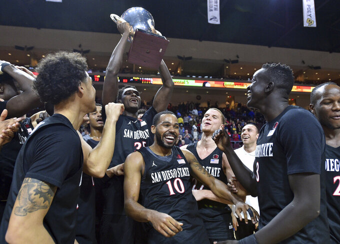 San Diego State guard KJ Feagin (10) and the team celebrate with the Las Vegas Invitational championship trophy after defeating Iowa in an NCAA college basketball game Friday, Nov. 29, 2019, in Las Vegas. (AP Photo/David Becker)