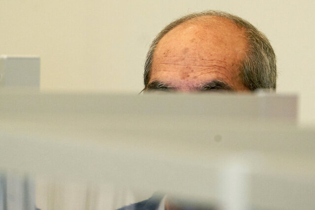 One of the defendants, Anwar R. (57), sits in the dock of the Higher Regional Court behind Corona protective screens, hiding his face under a hood in Koblenz, Germany, Thursday, April 23, 2020. Two former members of Syria's secret police go on trial Thursday in Germany accused of crimes against humanity for their role in a government-run detention center where large numbers of opposition protesters were tortured.(Thomas Frey/dpa via AP)