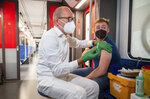 Christian Gravert, left, chief medical officer of the Deutsche Bahn, vaccinates a man with the Johnson & Johnson vaccine in a special train of the public transport S-Bahn, in which vaccination against COVID-19 are offered, in Berlin, Germany, Aug. 30, 2021. (Christophe Gateau/dpa via AP)