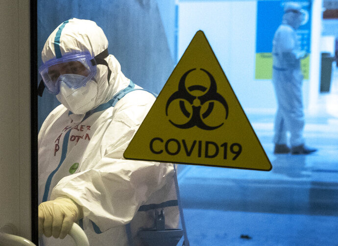 A medical worker wearing protective gear enters the treatment hall of a temporary hospital for coronavirus patients in the Krylatskoye Ice Palace in Moscow, Russia, Wednesday, Nov. 18, 2020. Russia's health care system has been under severe strain in recent weeks, as a resurgence of the coronavirus pandemic has swept the country. (AP Photo/Pavel Golovkin)