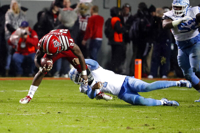 North Carolina State running back Zonovan Knight (24) tries to pull away from North Carolina's Myles Dorn (1) during the first half of an NCAA college football game in Raleigh, N.C., Saturday, Nov. 30, 2019. (AP Photo/Karl B DeBlaker)
