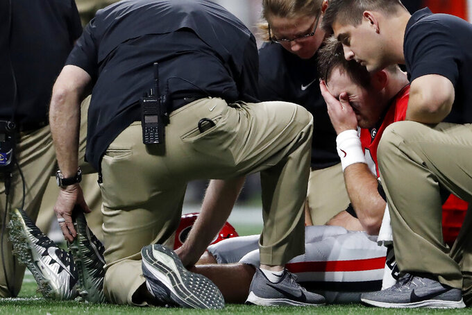 Georgia quarterback Jake Fromm (11) reacts as a medical team works during the first half of the Southeastern Conference championship NCAA college football game against LSU, Saturday, Dec. 7, 2019, in Atlanta. (AP Photo/John Bazemore)