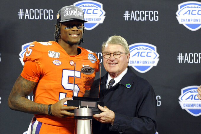 Clemson wide receiver Tee Higgins (5) receives the most valuable player trophy from ACC commissioner John Swofford during the second half of the Atlantic Coast Conference championship NCAA college football game in Charlotte, N.C., Saturday, Dec. 7, 2019. Clemson won 62-17. (AP Photo/Mike McCarn)