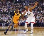 Utah Jazz's Emmanuel Mudiay (8) drives to the basket as Toronto Raptors' Norman Powell (24) defends during first half NBA basketball action in Toronto, Sunday, Dec. 1, 2019. (Hans Deryk/The Canadian Press via AP)