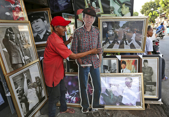 A vendor shows a cutout of Indonesian President Joko Widodo at his stall that sells portraits of Indonesian leaders, in Jakarta, Indonesia, Friday, Sept. 20, 2019. Widodo has asked lawmakers to delay a vote on a proposed new criminal code amid critics saying that the bill contains articles that may discriminate against minorities and violate freedom of speech. (AP Photo/Tatan Syuflana)