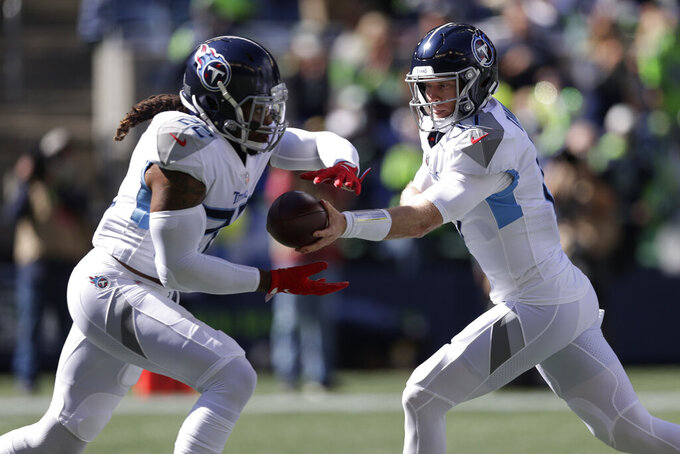 Tennessee Titans quarterback Ryan Tannehill, right, hands off to running back Derrick Henry during the first half of an NFL football game, Sunday, Sept. 19, 2021, in Seattle. (AP Photo/John Froschauer)