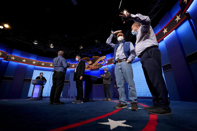 Production crew member stand on stage ahead of the final presidential debate between Republican candidate President Donald Trump and Democratic candidate former Vice President Joe Biden, Wednesday, Oct. 21, 2020, in Nashville, Tenn. The debate will take place Thursday, Oct. 22 at the Curb Event Center at Belmont University. (AP Photo/Julio Cortez)