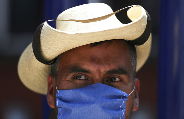 A street vendor wears a mask over his mouth as a precaution against the spread of the new coronavirus in Mexico City, Friday, Feb. 28, 2020. Mexico's assistant health secretary announced Friday that the country now has confirmed cases of the COVID-19 virus. (AP Photo/Fernando Llano)