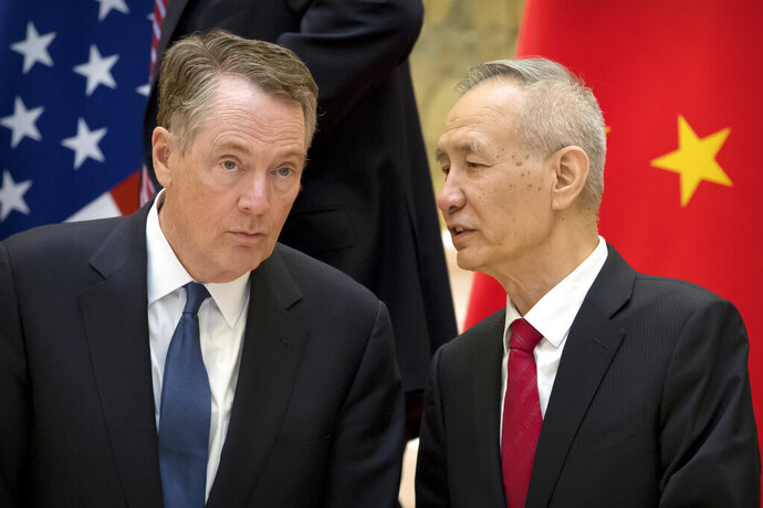 FILE - In this Feb. 15, 2019, file photo, Chinese Vice Premier Liu He, right, talks with U.S. Trade Representative Robert Lighthizer, while they line up for a group photo at the Diaoyutai State Guesthouse in Beijing. China's economy czar is going to Washington for talks Thursday and Friday aimed at ending a tariff war over Beijing's technology ambitions.(AP Photo/Mark Schiefelbein, File)