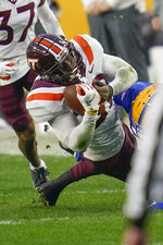 Virginia Tech defensive back Chamarri Conner (22) twists away frpom Pittsburgh wide receiver Tre Tipton (6) after intercepting a pass during the first half of an NCAA college football game, Saturday, Nov. 21, 2020, in Pittsburgh. (AP Photo/Keith Srakocic)
