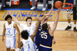 Notre Dame forward Matt Zona (25) takes a shot as North Carolina guard Leaky Black (1) and teammate forward Walker Kessler, top, during the second half of an NCAA college basketball game in the second round of the Atlantic Coast Conference tournament in Greensboro, N.C., Wednesday, March 10, 2021. (AP Photo/Gerry Broome)