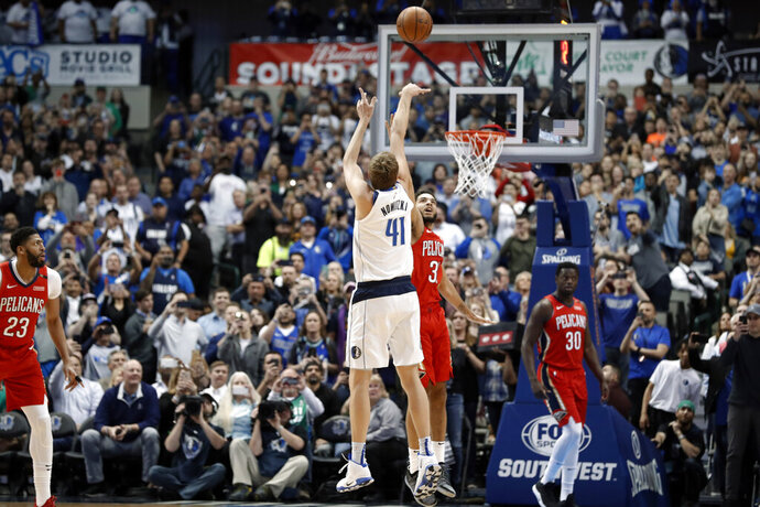 Dallas Mavericks forward Dirk Nowitzki (41) shoots as New Orleans Pelicans' Kenrich Williams (3) defends and Pelicans' Julius Randle (30) and Anthony Davis (23) watch in the first half of an NBA basketball game in Dallas, Monday, March 18, 2019. With the basket, Nowitzki became the NBA's sixth-leading scorer. (AP Photo/Tony Gutierrez)