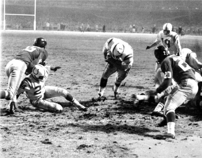 FILE -  In this Dec. 28, 1958, file photo, Baltimore Colts fullback Alan Ameche advances through a big opening provided by teammates to score the winning touchdown in overtime against the New York Giants during the NFL championship football game at Yankee Stadium in New York. Colts' Lenny Moore gets a block on Giants' Emlen Tunnell (45) at left. Colts quarterback Johnny Unitas (19) is at right along with Giants' Jim Patton (20). The Colts won 23-17. The 1958 championship matchup was voted the best game as part of the NFL's celebration of its 100th season. (AP Photo/File)