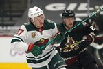 FILE - In this Monday, April 19, 2021 file photo, Minnesota Wild left wing Kirill Kaprizov (97) and Arizona Coyotes left wing Johan Larsson (22) skate down ice during the first period of an NHL hockey game in Glendale, Ariz. Kirill Kaprizov not only is the top scoring rookie in the NHL, he's also Minnesota's hottest player as the Wild look to win their first playoff series since 2015. (AP Photo/Ross D. Franklin, File)