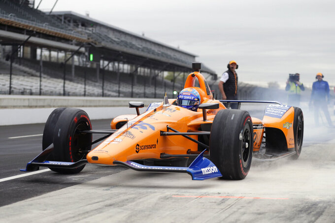 FILE - In this April 24, 2019, file photo, IndyCar driver Fernando Alonso, of Spain, drives out of the pit area during testing at the Indianapolis Motor Speedway in Indianapolis. Alonso will once again attempt to complete motorsports' version of the Triple Crown with a return to the Indianapolis 500 in May with McLaren. (AP Photo/Michael Conroy, File)