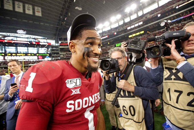 Oklahoma quarterback Jalen Hurts (1) smiles after putting on his conference championship hat after Oklahoma's 30-23 overtime victory over Baylor in an NCAA college football game for the Big 12 Conference championship, Saturday, Dec. 7, 2019, in Arlington, Texas. (AP Photo/Jeffrey McWhorter)