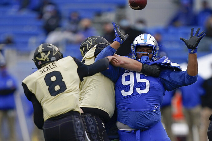 Kentucky defensive tackle Quinton Bohanna (95) pressures Vanderbilt quarterback Ken Seals (8) during the second half of an NCAA college football game, Saturday, Nov. 14, 2020, in Lexington, Ky. (AP Photo/Bryan Woolston)
