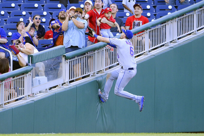 New York Mets left fielder Jeff McNeil (6) climbs the wall for a foul ball by Washington Nationals' Andrew Stevenson during the ninth inning of the first baseball game of a doubleheader, Saturday, Sept. 4, 2021, in Washington. The Mets won 11-9 in extra innings. (AP Photo/Nick Wass)