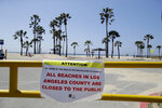 A closure sign is placed at the entrance of a beach front parking lot Sunday, March 29, 2020, in the Venice beach section of Los Angeles. With cases of coronavirus surging and the death toll increasing, lawmakers are pleading with cooped-up Californians to spend a second weekend at home to slow the spread of the infections. (AP Photo/Marcio Jose Sanchez)