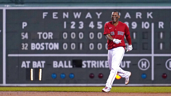 Boston Red Sox's Rafael Devers looks toward teammates while celebrating after his winning RBI-single in the bottom of the ninth inning of a baseball game against the Toronto Blue Jays at Fenway Park, Monday, June 14, 2021, in Boston. (AP Photo/Charles Krupa)